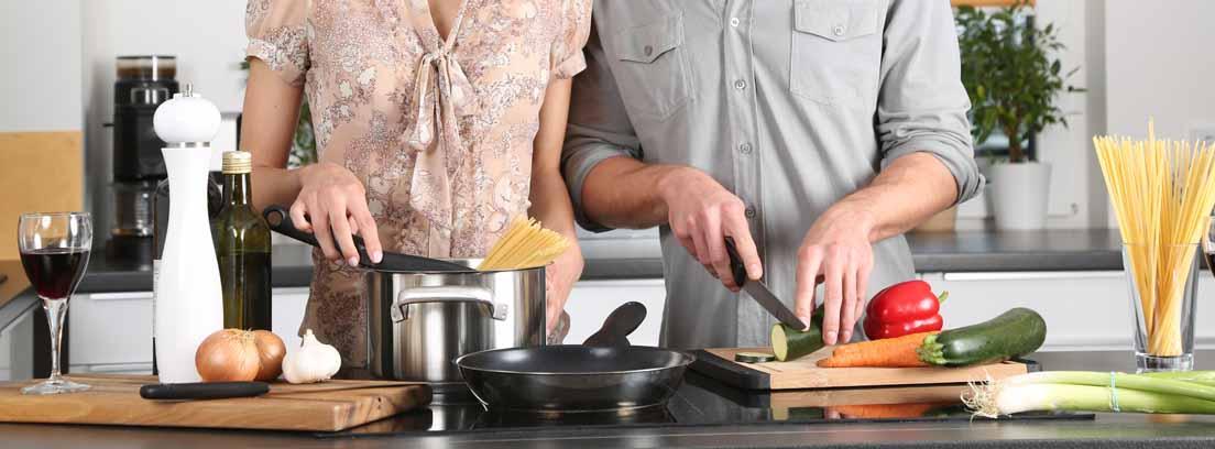 Hombre y mujer en la cocina preparando una olla con espaguetis y verdura