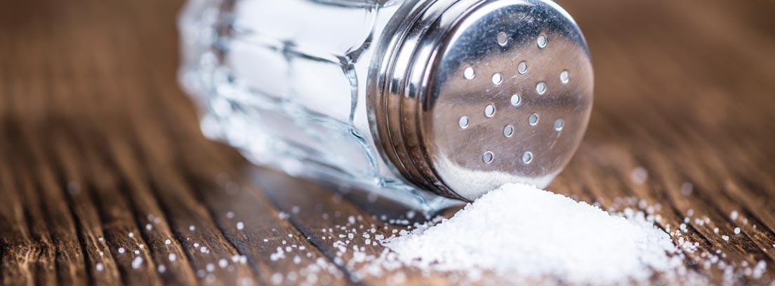 Salero en horizontal con la sal derramada por la superficie