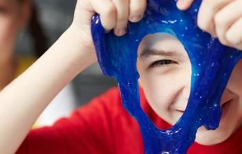 Niños jugando con un slime de color azul