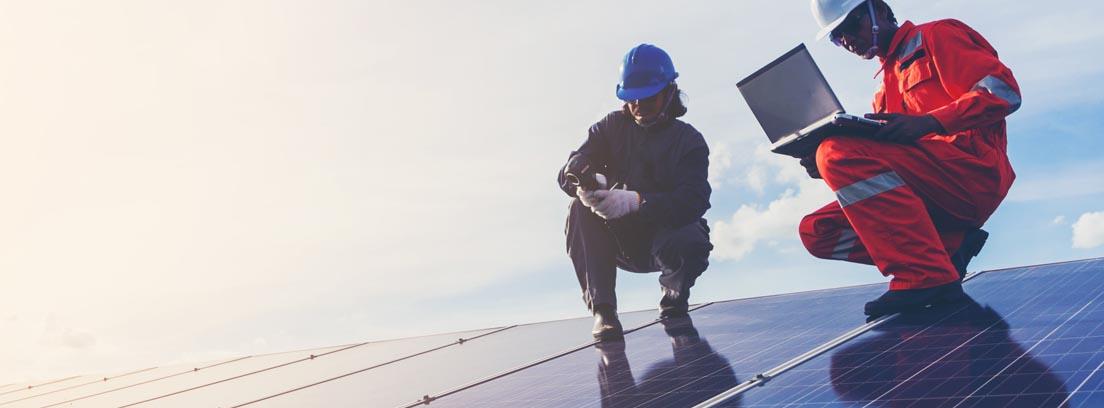 Operarios con cascos y monos sobre instalación de placas solares