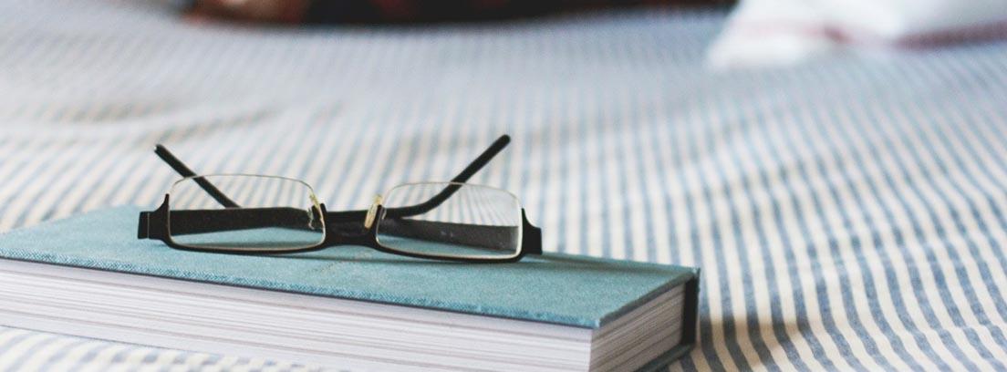 Gafas sobre un libro en una cama con una colcha de colores suaves