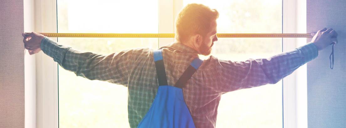 Hombre midiendo una ventana para instalar estores