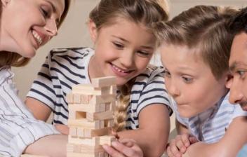 Dos adultos y don niños sonriente alrededor de una mesa disfrutando de uno de los mejores juegos para jugar en familia en casa