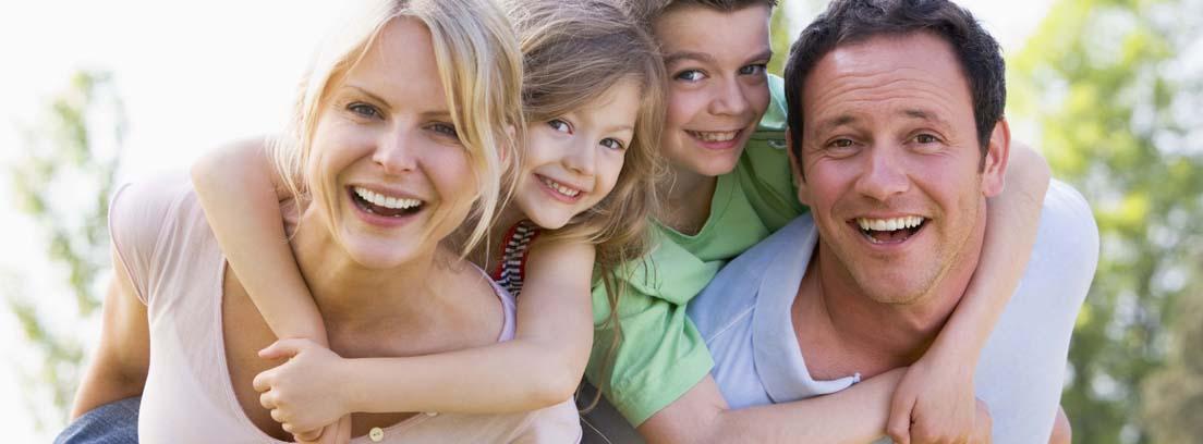 Hombre y mujer sonrientes llevando cada uno a un niño y a una niña en al espalda