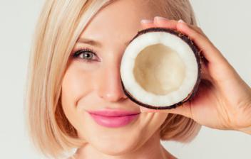 Mujer sonriente poniéndose medio coco delante del ojo
