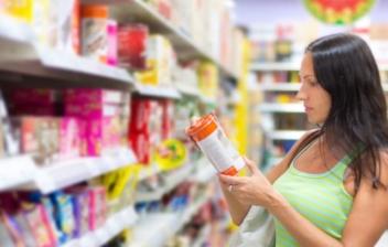 Mujer al lado de una estantería de un supermercado mirando la etiqueta Nutriscore de un producto
