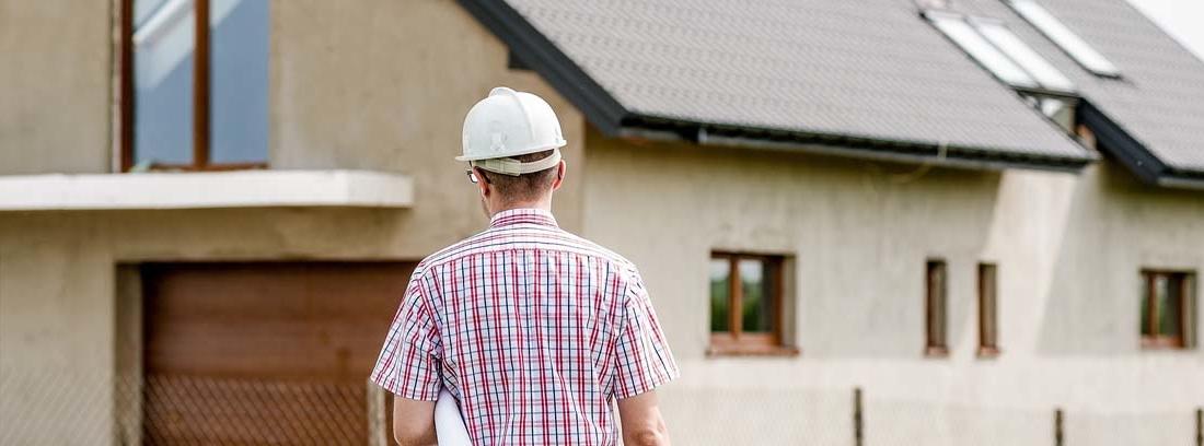 Hombre con casco con planos bajo el brazo frente a una casa en construcción