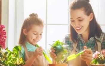 Mujer y niña sonrientes con delantales realizando labores de jardinería frente a una mesa llena de macetas con plantas de invierno con flores