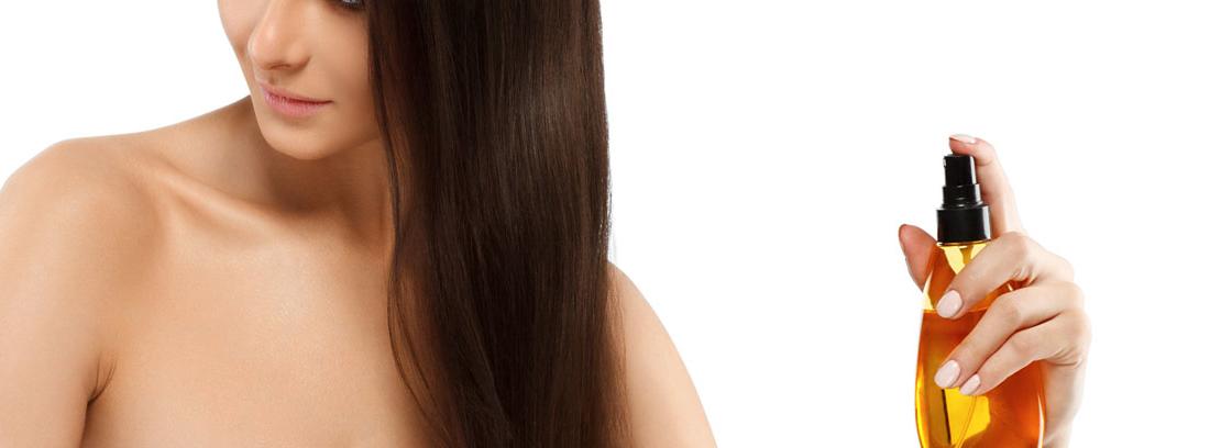 Mujer usando un espray con aceite de argán para el pelo