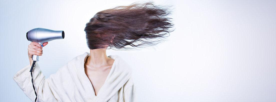 Mujer secando su pelo con un secador