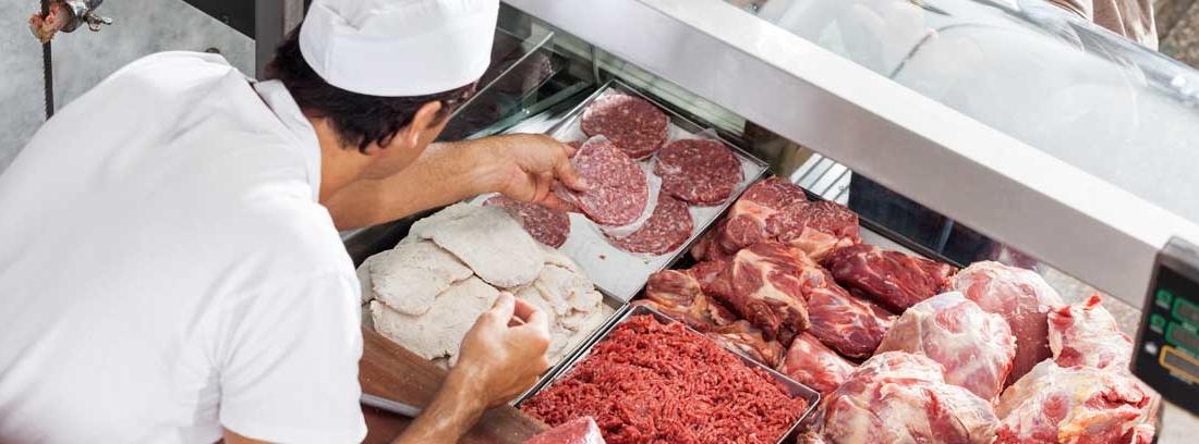 Mujer frente a mostrador con diferentes tipos de carnes.