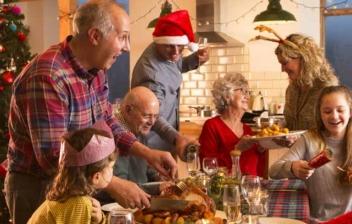 Adultos y niños alrededor de una mesa con comida y adornos de Navidad