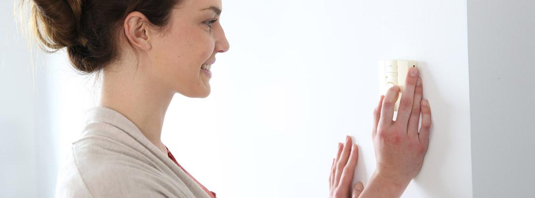 Mujer ajustando la temperatura en un termostato digital