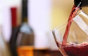 Botella vertiendo vino en una copa, y varias copas y botellas al fondo