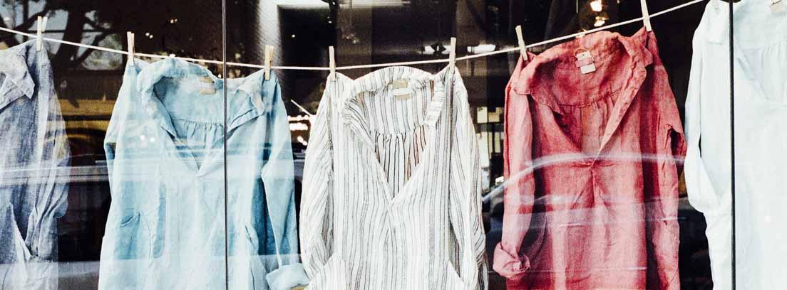 Camisas tendidas en una cuerda, todas de colores claros y una de color rojo