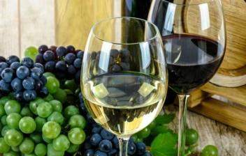 Dos copas de vino tinto y blanco sobre una mesa con uvas