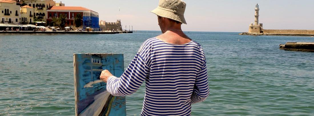Hombre delante del mar pintando un cuadro al óleo