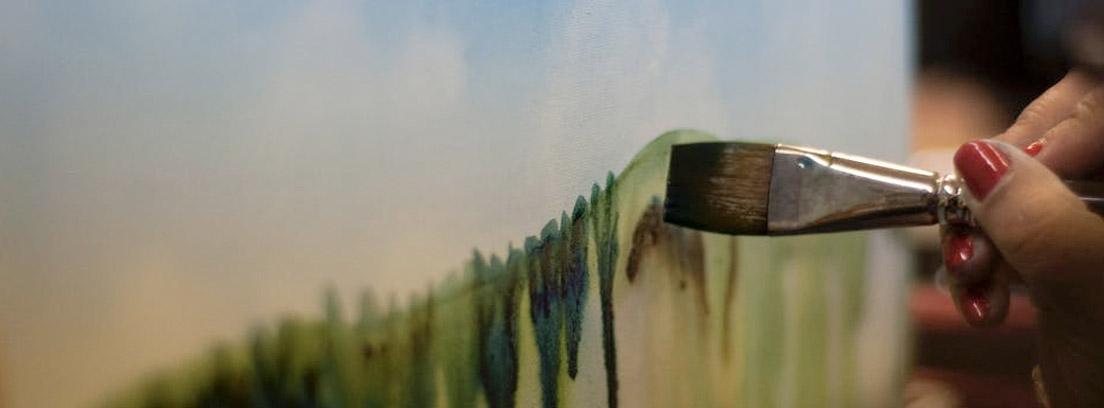 Mano con pincel con óleo sobre un lienzo