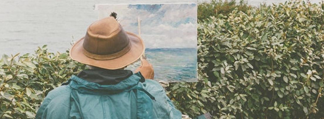 Persona delante de lienzo con pincel