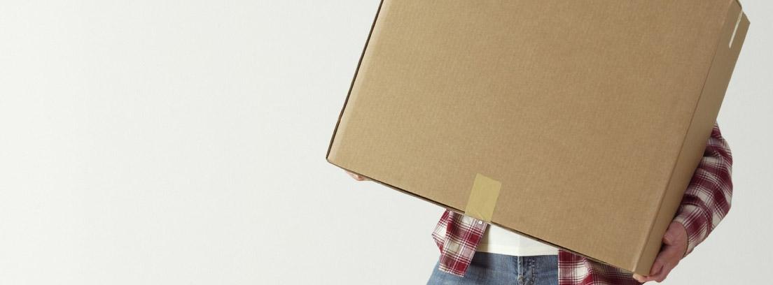 Persona sujetando varias cajas de cartón porque ha decidido no elegir una empresa de mudanzas