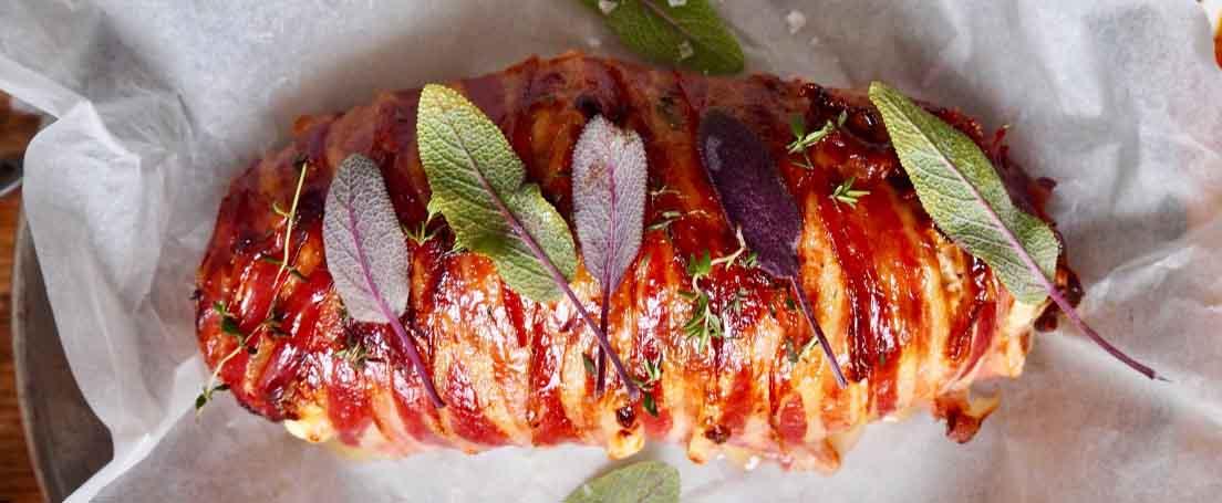 Redondo de carne picada envuelto en lonchas de beicon con hojas
