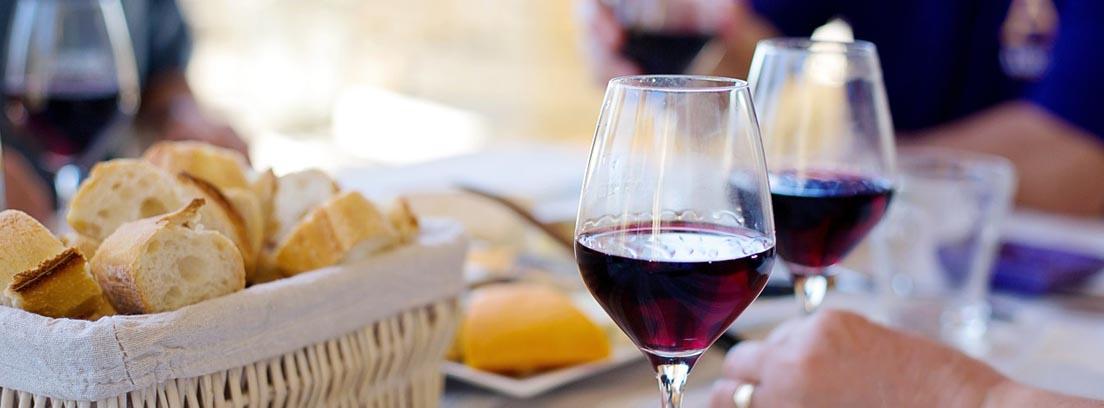 Mano sosteniendo una copa de vino durante una comida