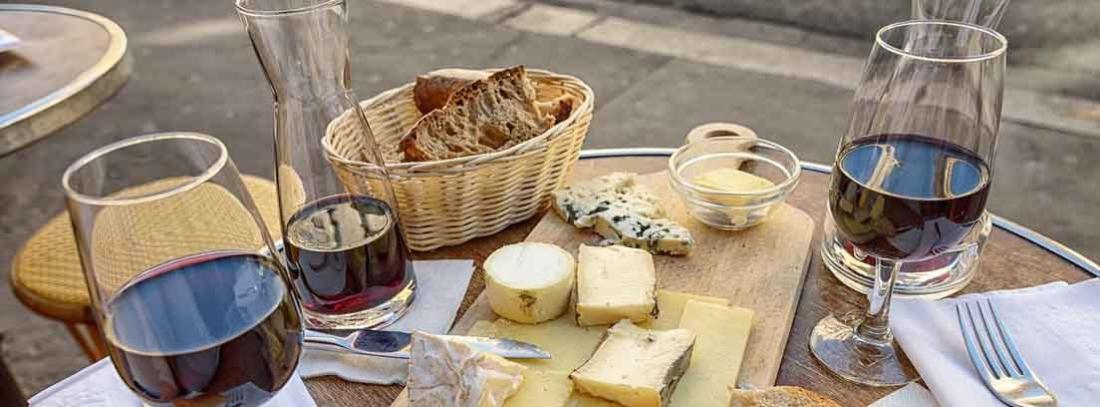 Distintos tipos de queso con copas de vino tinto