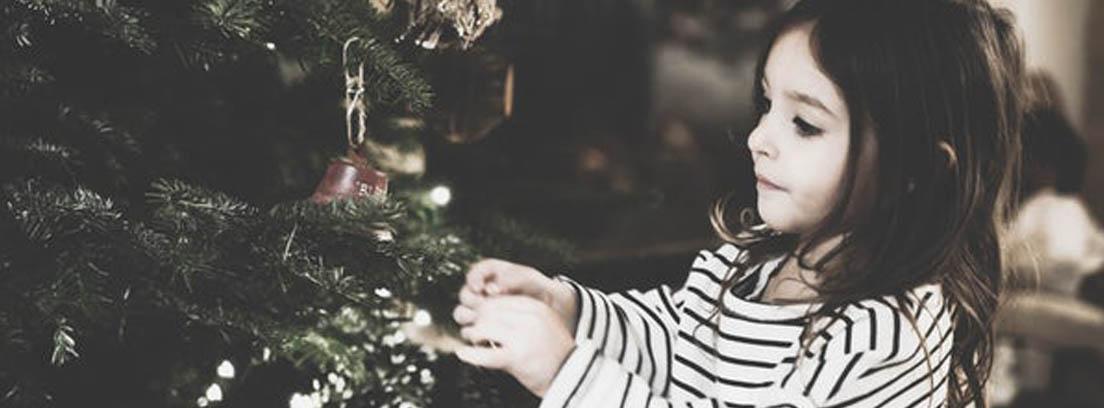 Niña adornando árbol de Navidad