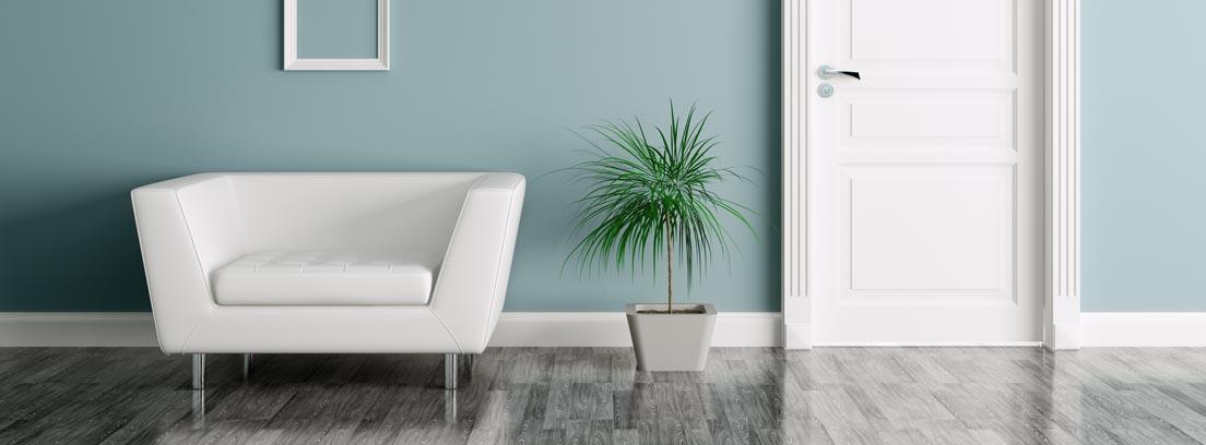 Sillón, marcos y puerta blancos sobre una pared azul