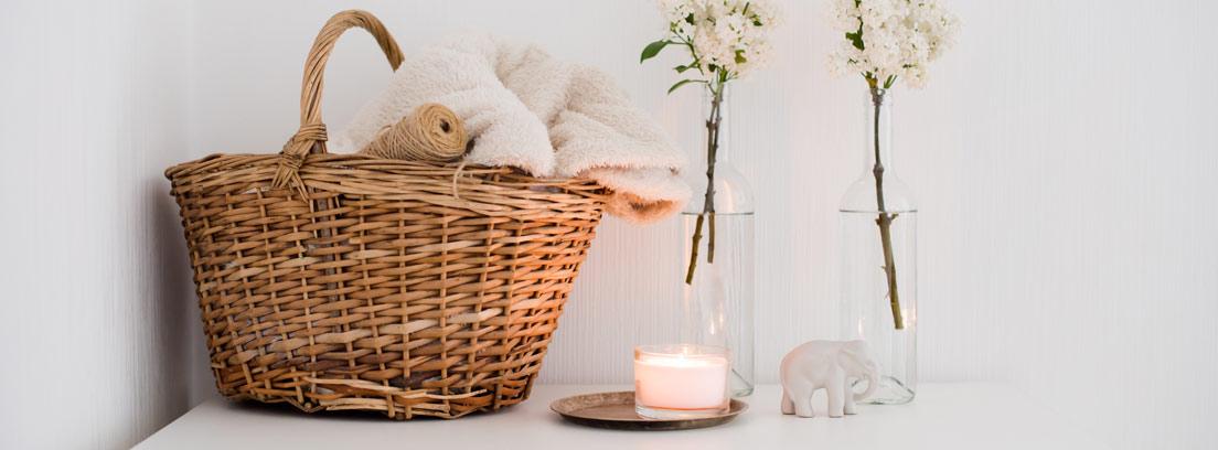 Cesta con toallas, botellas con flores y velas después de aprender cómo hacer cestas de mimbre para decorar