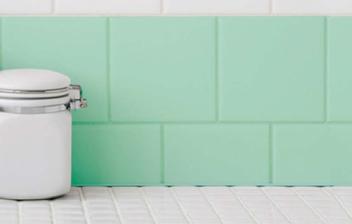 Tarros de cerámica delante de una pared en la que se han pintado azulejos de la cocina