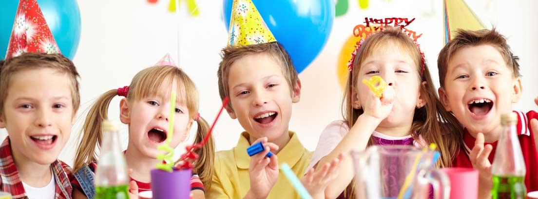 Varios niños sonrientes con gorros de cumpleaños detrás de una mesa con merineda y decoración de globos