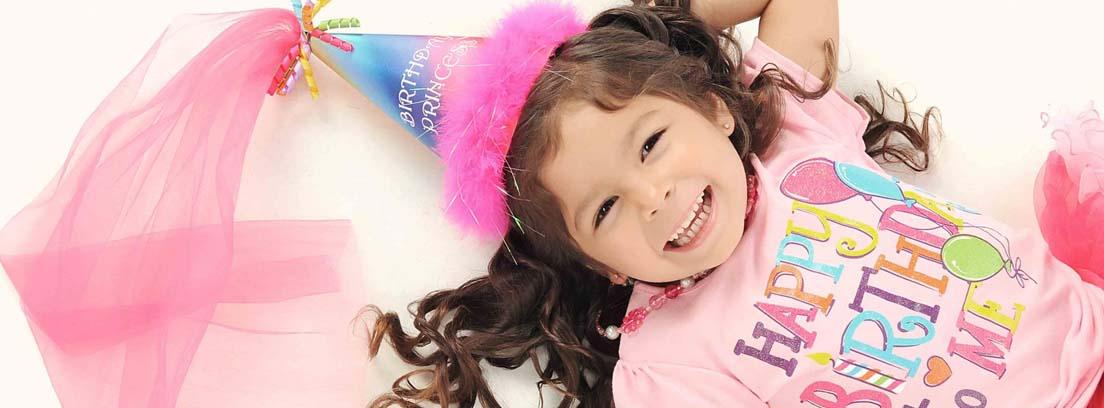 """Niña sonriente con gorro de cumpleaños y camiseta en la que se lee: """"Happy birthday to me"""""""