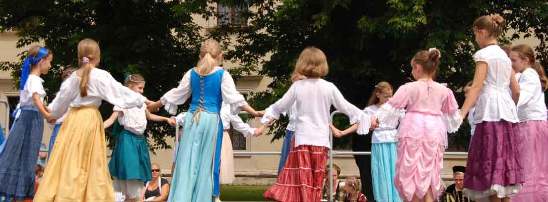 Varias niñas con disfraces dadas de la mano formando un corro