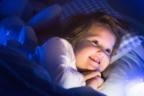 Niña sonriente en la cama con luces infantiles para combatir el miedo a la oscuridad