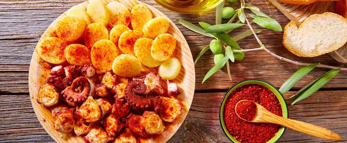 Vista cenital de un plato de pulpo a la gallega y patatas y un cuenco con pimentón