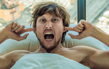 Hombre en la cama al lado de una ventana, gritando con los dedos tapándose los oídos