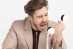 Persona gritando delante de un auricular de teléfono