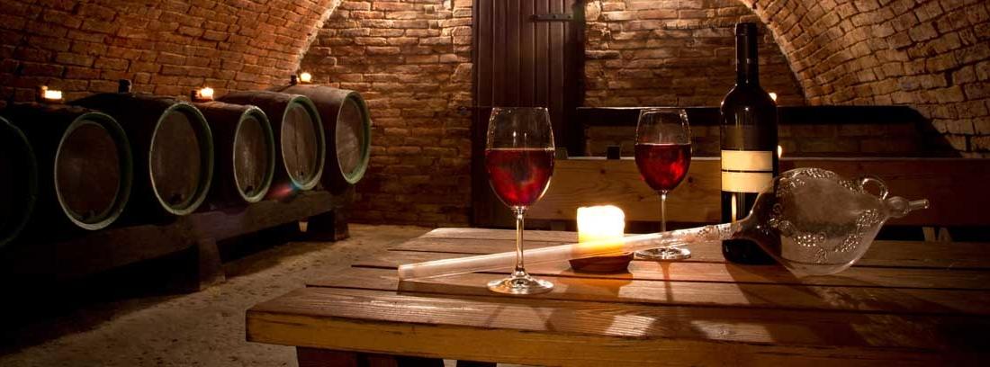 Una de las mejores bodegas con barricas, mesa y copas de vino