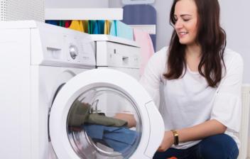 Mujer poniendo ropa dentro de una lavadora
