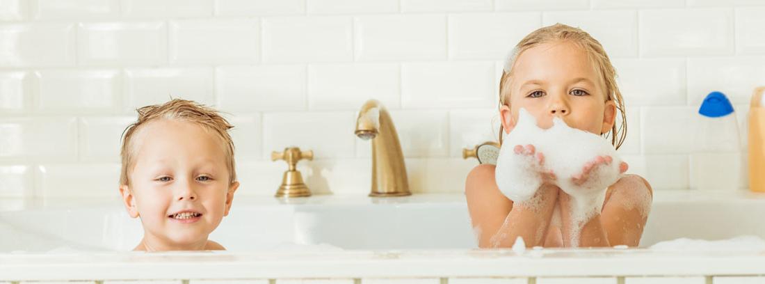 Dos niños dentro de una bañera con espuma