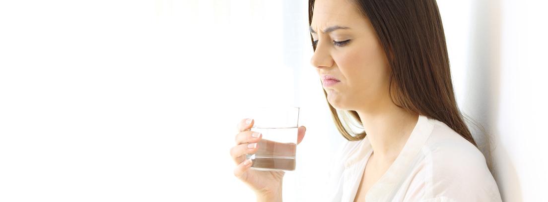 mujer con un vaso de agua con mal sabor