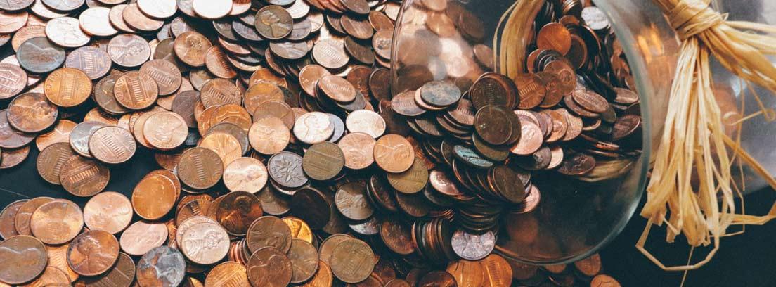 Tarro de cristal junto a monedas antiguas
