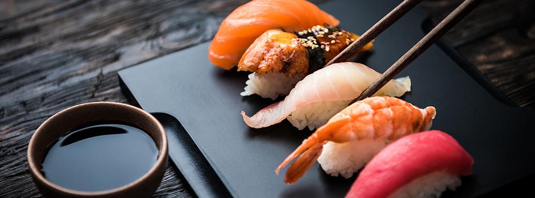 cuatro piezas de nigiri-shushi acompañado de salsa de soja