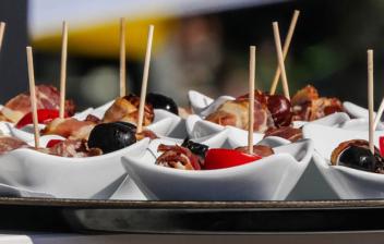 Diferentes platos pequeños con aperitivos con palillo