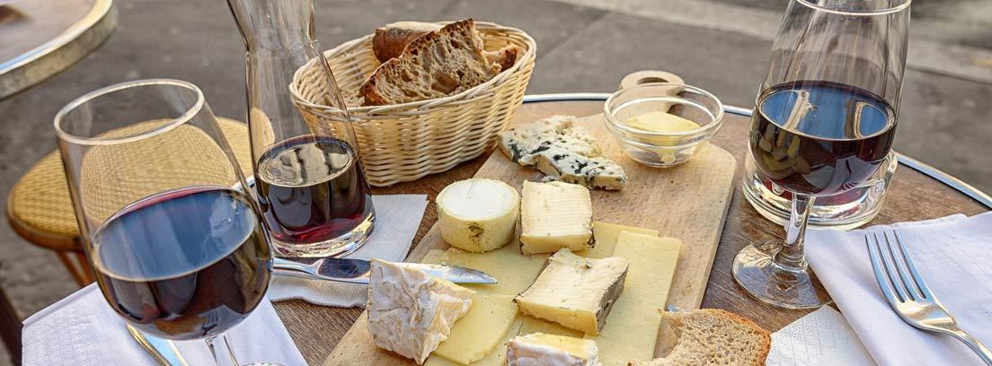 Aperitivo sencillo con tabla de quesos y copas de vino tinto.