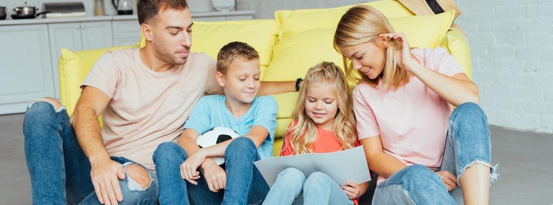 Dos adultos y dos niños sentados en el suelo mirando sonrientes un papel