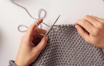 Vista cenital de unas manos con agujas de coser tejiendo una prenda con lana gris