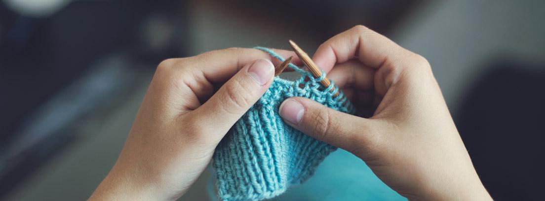 Manos con agujas de tener tejiendo lana azul