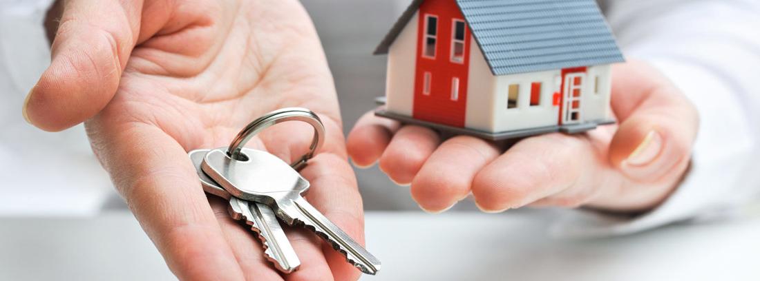 Manos extendidas con unas llaves y la maqueta de una casa